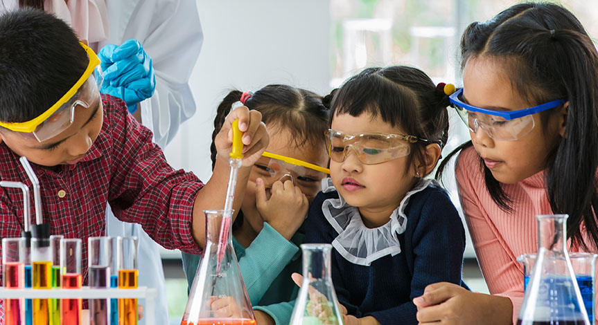 Boy drops something into orange beaker using a pipette in a lab while 3 little girls watch all wearing safety goggles