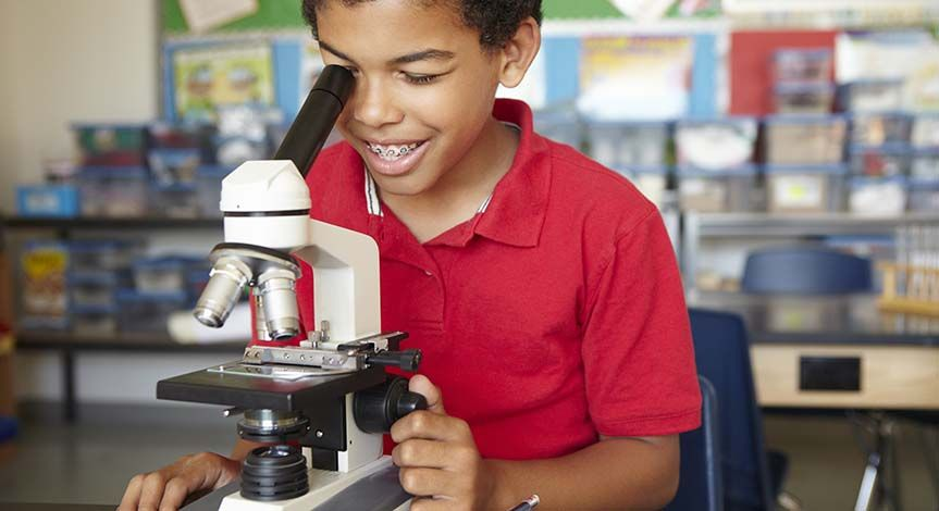 Boy in red shirt looking though a microscope in a classroom