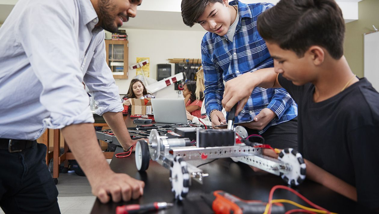 STEM coach with male students building robotic vehicle