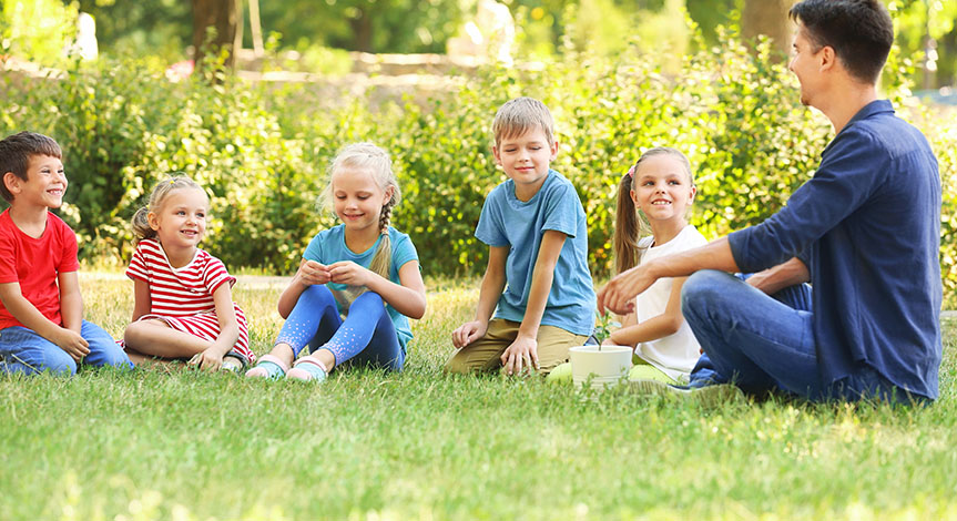Group of children with teacher sitting on the grass in park on sunny day